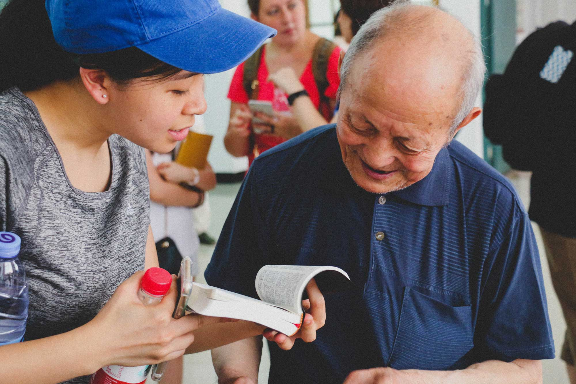 China Missions team member handing out a Bible.