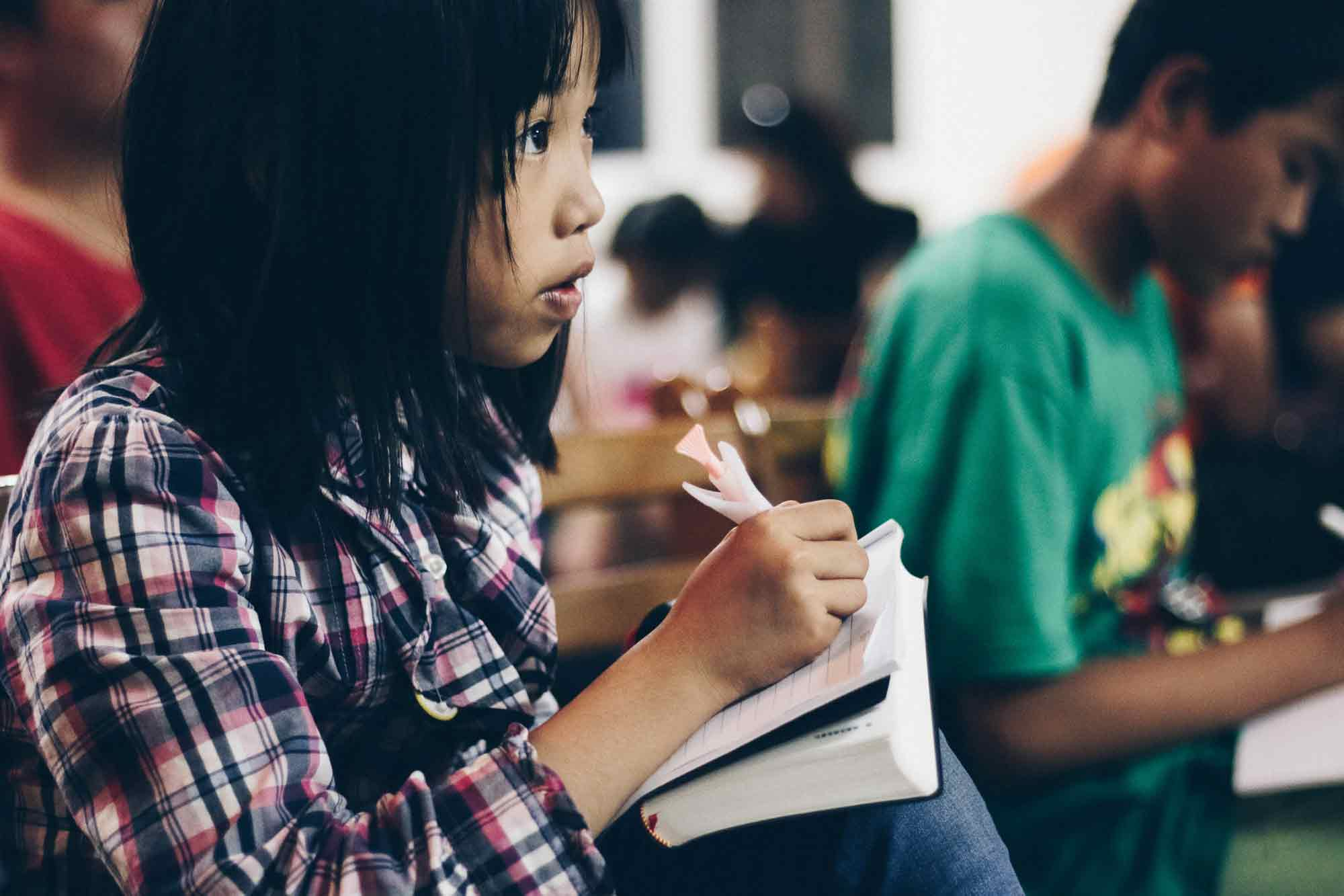 A girl taking notes with her new Bible.
