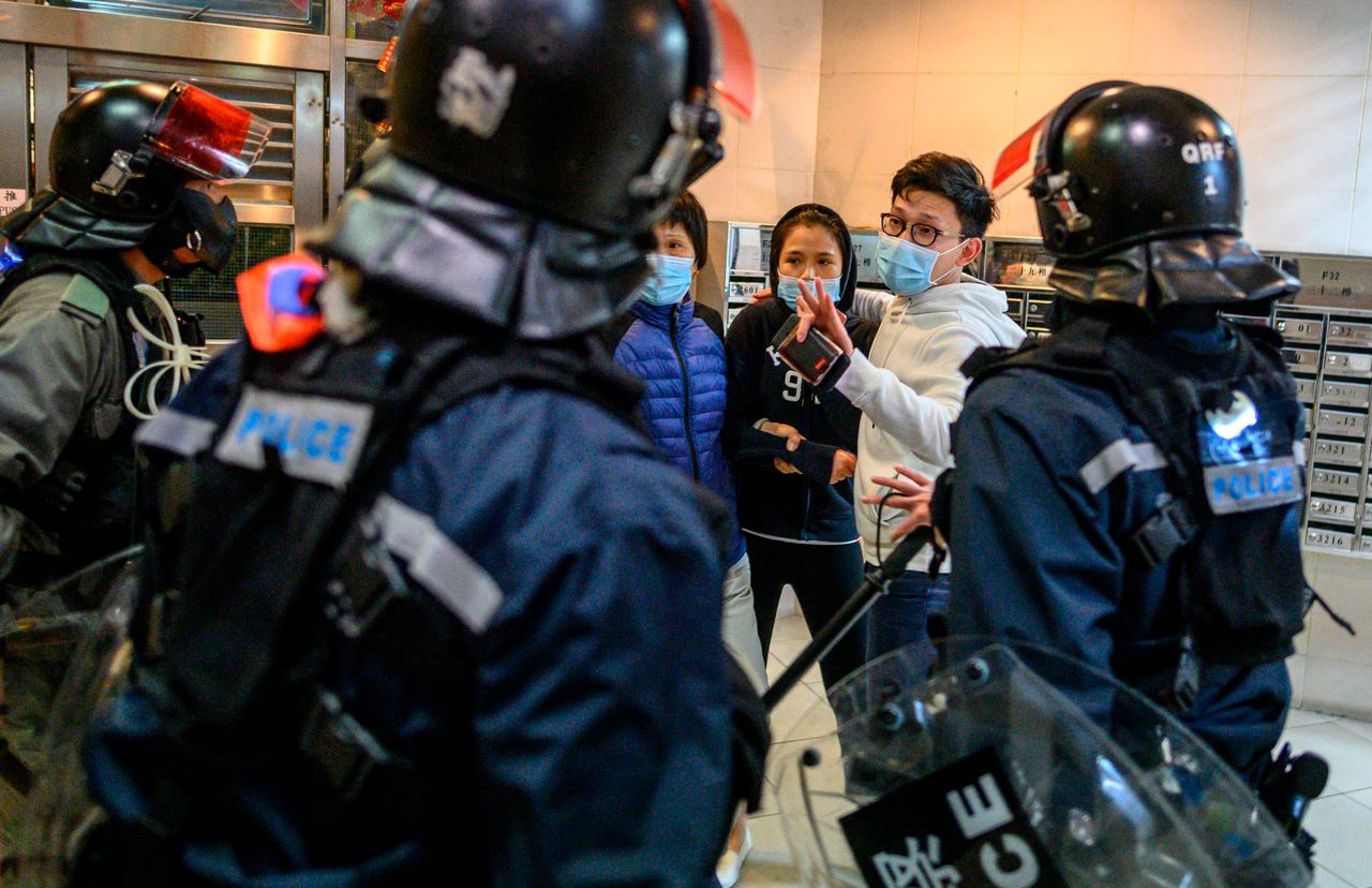 Hong Kong riot police are still stopping and inspecting the belongings of suspected individuals during the virus outbreak.